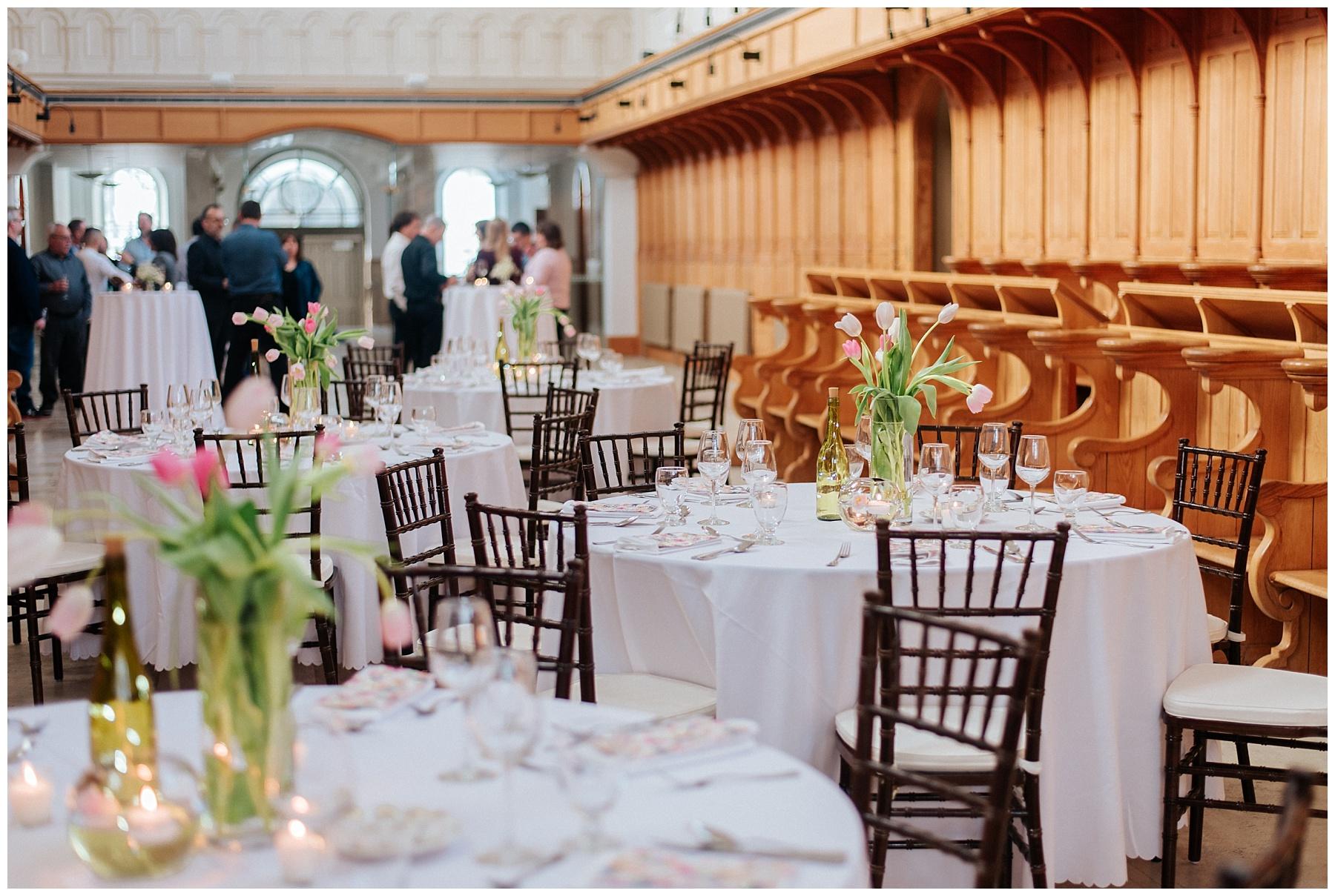 Des tulipes décorent les tables de la salle de réception de l'Abbaye d'Oka alors que des chaises chiavari brunes attendent les invités.