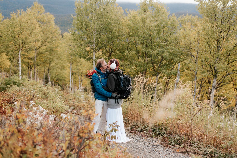 Couple de mariés s'embrasse sur le sentier vers leur elopement au lever du soleil en Gaspésie.