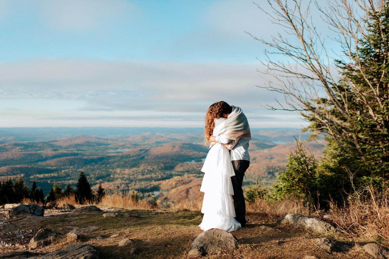 Couple se serrent dans leurs bras pour se réchauffer lors de leur elopement d'automne au lever du soleil dans les Laurentides.