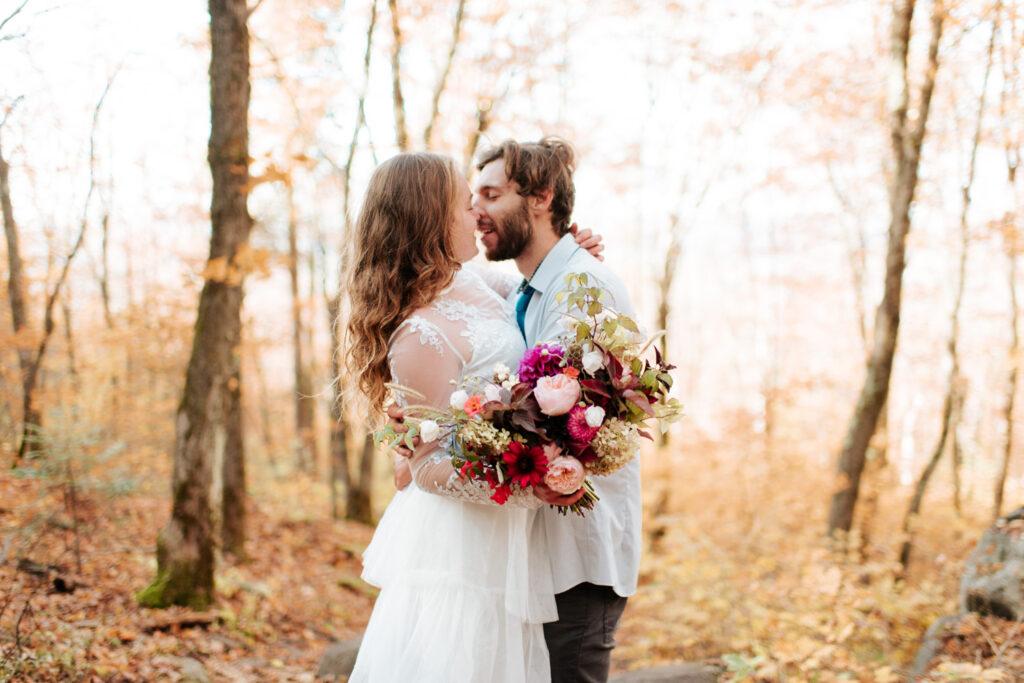 Couple de mariés s'embrassent dans une foret des Laurentides