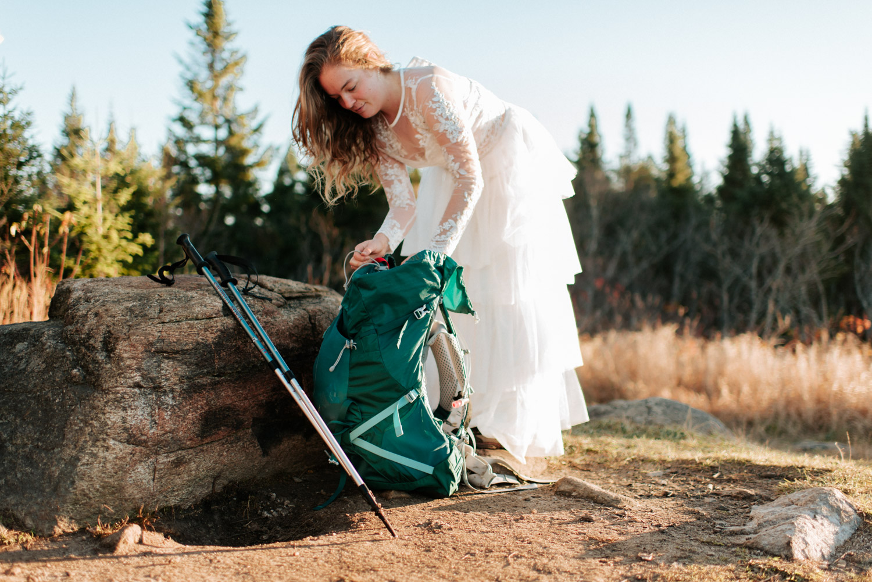 Mariée prépare son sac à dos d'expédition pour son elopement au sommet d'une Montagne dans les Laurentides