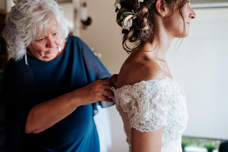Mère de la mariée aide sa fille à attacher sa robe de mariage avant son elopement dans Lanaudière.
