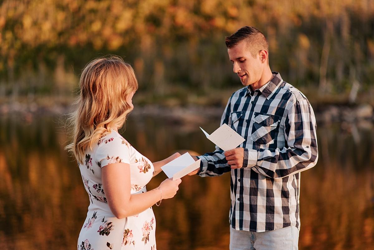 Elopement en Gaspésie alors que les deux mariés lisent leurs voeux de mariage. Les montagnes sont derrière eux.