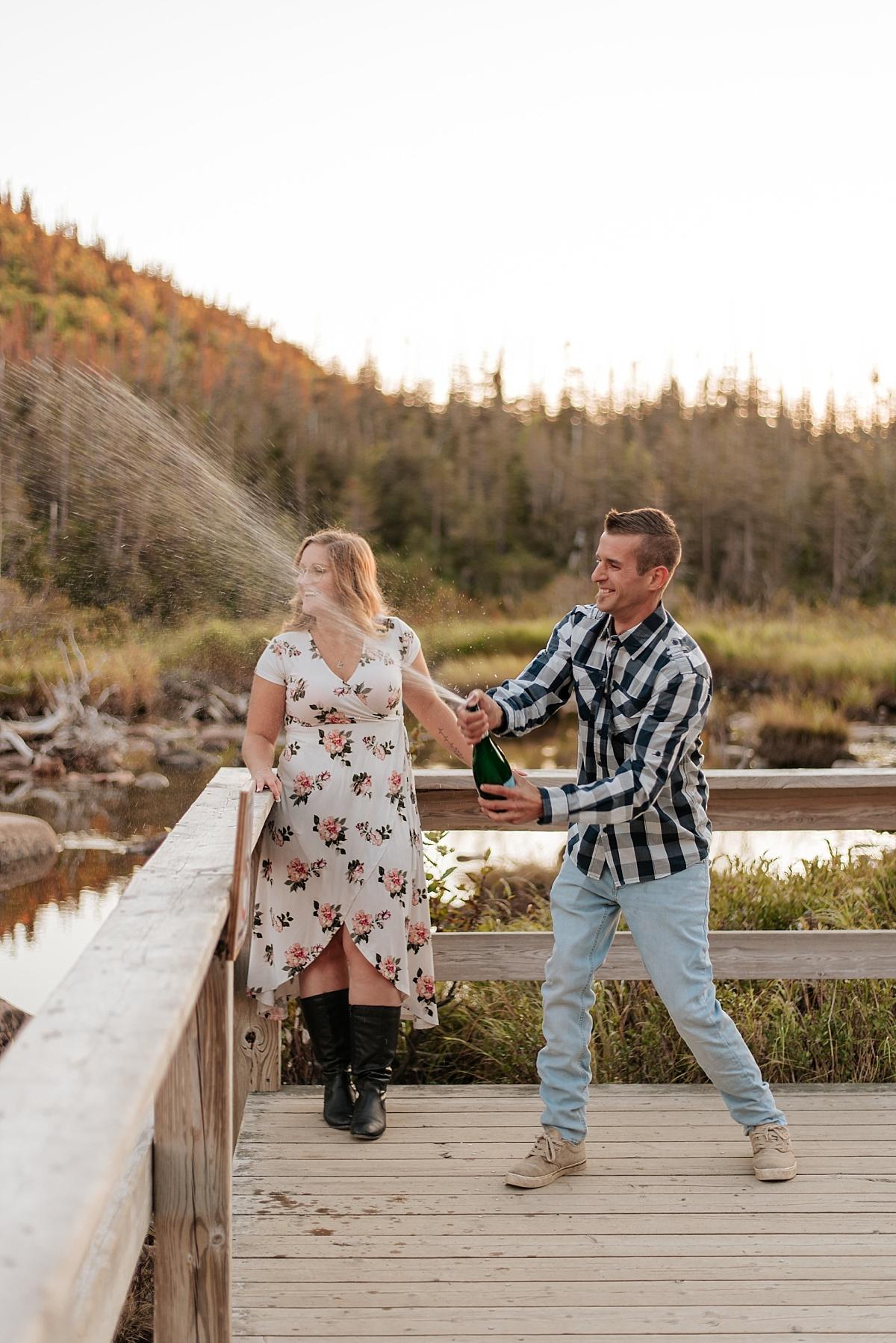 Le couple de mariés ouvre une bouteille de mousseux sur le quai après leur elopement en gaspésie.
