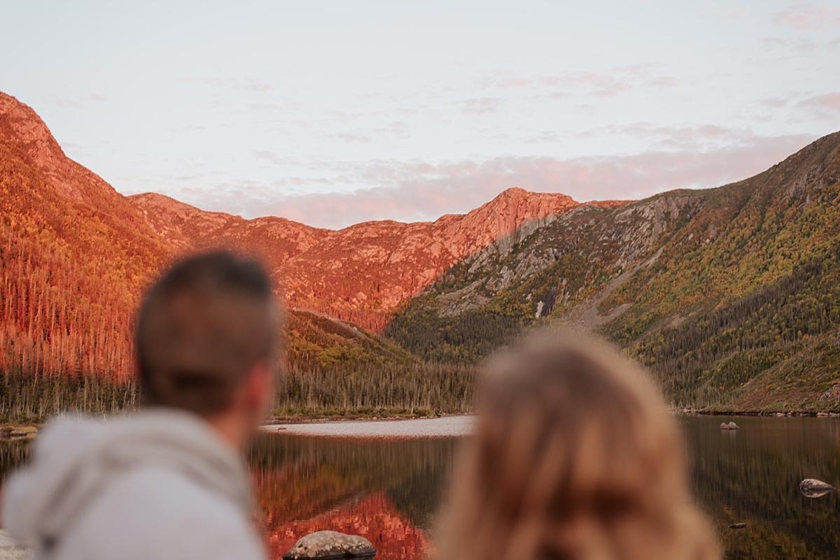 Les deux mariés regardent les montagnes illuminées par leu coucher du soleil.